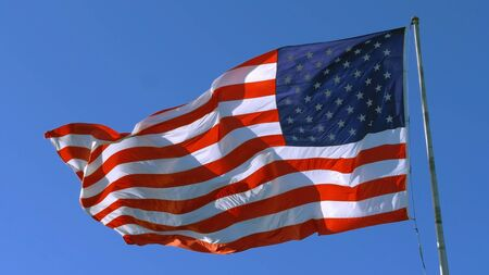 USA flag on flagpole. American flag - symbol of freedom and law in the USA. American flag flies in the sky as a symbol of the Great Country of the USA. Big American flag against blue sky.
