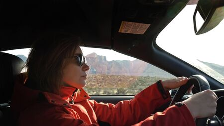 Young woman is driving a car on a sunny day, outside the window is a mountain landscape the Red Rock Canyon. Woman in a red jacket driving, close up. Woman with a serious look driving a car.