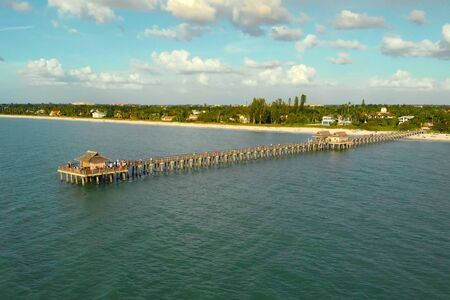 Drone flies near a pier in Naples, Florida at sunset time, aerial view. Drone flies around a fishing pier in Naples, Florida USA. Long wooden pier at sea. Ocean fishing pier, aerial view.
