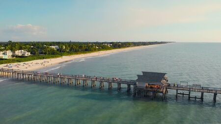 Coast and the beach near the pier leaving into the ocean. Naples, Florida is a tourist town in the USA. Pier in Naples by Aerial Drone. Beach near the ocean pier.