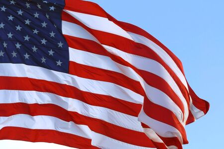 American Flag Waving in the Wind. Close up of large American flag waving in front of blue sky. Close up of an American flag flying in the wind against a background of clear sky. 스톡 콘텐츠