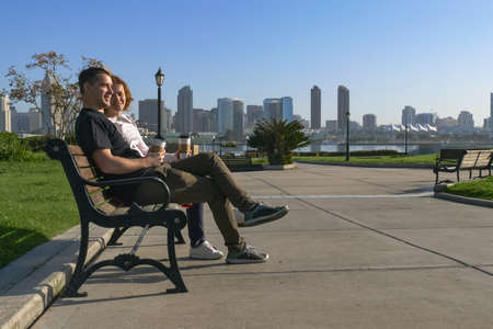 Young couple is sitting on a bench in the city, the sun is shining, they are talking and laughing, watching the distance and dreaming. In the background is the downtown San Diego with skyscrapers.