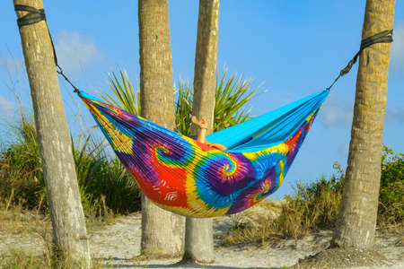 Lesbian couple relaxing in rainbow hammock at sunset. Two lesbians hid in a cozy hammock of rainbow colors on the beach. Young couple in love relaxing in hammock by beach. Lesbian couple retired.
