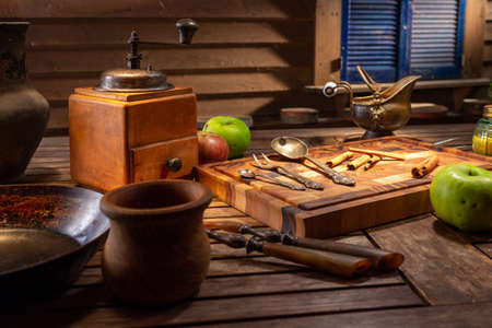 Vintage tablespoons and forks. Vintage still life with antique dishes and green apples. Rustic wooden old coffee grinder.