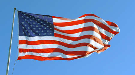 American Flag blowing in the wind with a blue sky, USA American Flag. Waving United states of America famous flag in front of blue sky. Independence Day, Labor day, Flag Day - American Celebration 免版税图像