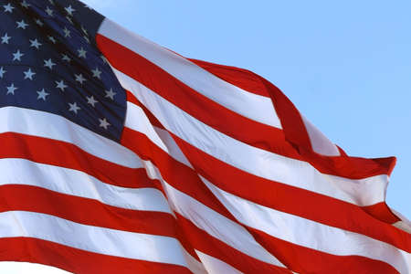 Large American flag gently waving in the wind. American Flag Waving Under A Blue Sky With Clouds. Real Big Flag of the USA waving in the wind. Real Flag of the USA waving.