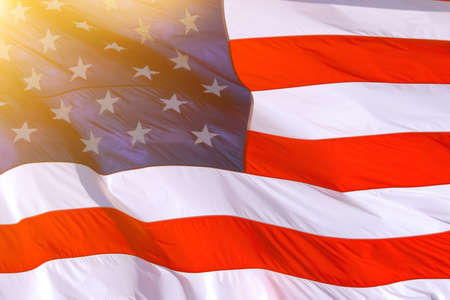 AMERICAN FLAG BACKGROUND: American flag USA Close Up waving background texture. American Flag Waving Slow Motion. Beautifully waving star and striped American flag. Lens Optical Flare 免版税图像
