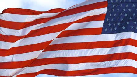 American flag waving in wind, video footage. USA flag flaping in wind. Realistic USA Flag background. Waved highly detailed fabric texture. American flag flying in the wind at sunny day. Election day.