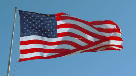 American USA flag on a flagpole waving in the wind against a clear blue sky on a sunny day. Standard-Bild