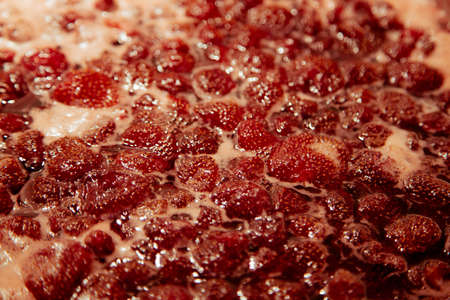 Strawberry jam simmering slightly, detailed close-up, top view. Beautiful strawberry jam in cooking process. Boiling homemade strawberry jam. Making a homemade Strawberry Jam. Boiling fruit into a pan