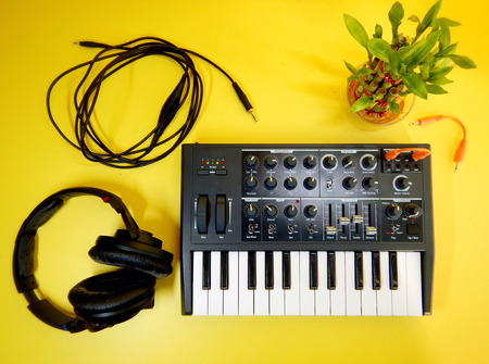 Synthesizer on yellow background with orange patch cables and headphones Stock Photo