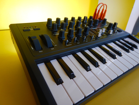 Synthesizer on yellow background with orange patch cables