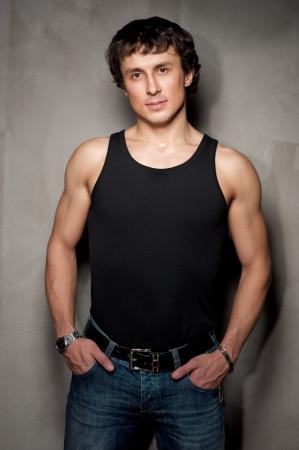 muscle shirt: Retrato de un apuesto joven de pie con pared gris Foto de archivo