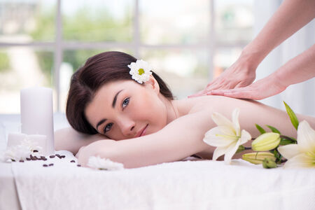 Relaxed woman with flowers in spa center enjoying massage Stock Photo