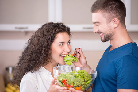 Portrait of a happy couple preparing and eating salad in kitchen photo