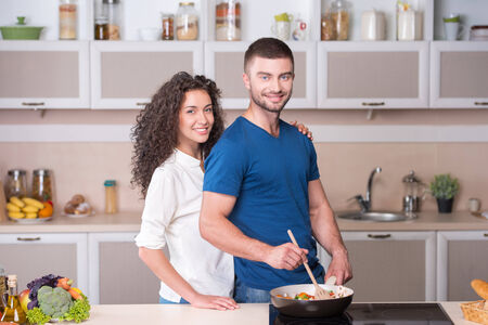 Portrait of a beautiful couple preparing supper together in kitchen photo