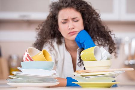 Retrato de uma dona de casa descontente secagem pratos