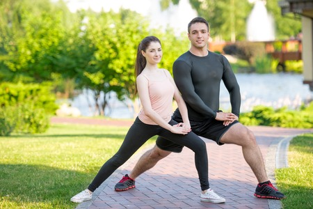 Portrait of a sporty couple doing stretching in the park at sunny day