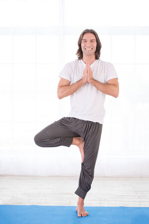 Smiling young man practicing yoga, doing tree pose photo