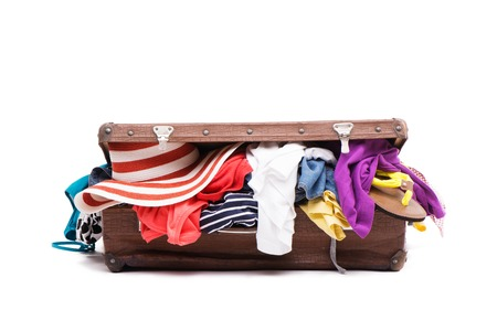 packing suitcase: Vintage suitcase is full of travel stuff and clothes, isolated on white background