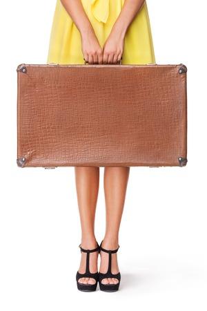 mujer con maleta: La muchacha se coloca con la maleta de �poca antigua, aislada en el fondo blanco Foto de archivo