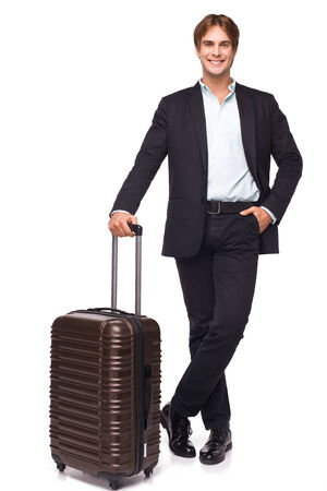 business traveler: Business traveler smiling and standing with his luggage