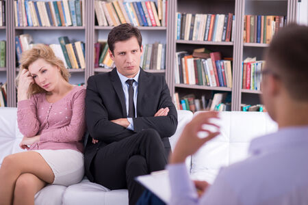 couples therapy: Portrait of a Unhappy couple talking to the psychologist and sitting on the couch