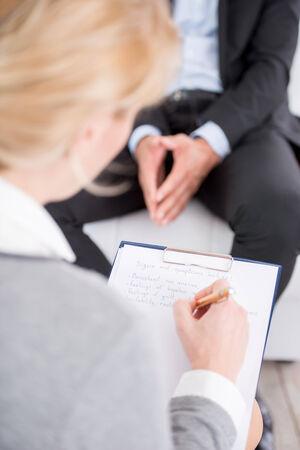 terapia psicologica: Retrato de un psic�logo haciendo Notas femeninas durante la sesi�n de terapia psicol�gica