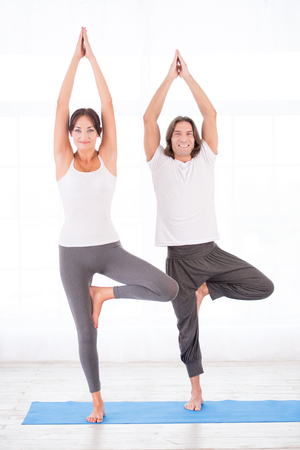 Smiling young couple practicing yoga, doing tree pose Stock fotó