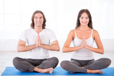 Smiling young couple meditating in lotus pose, sitting on blue c