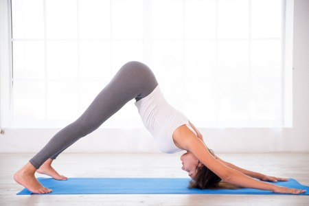 Relaxed young woman practicing yoga, doing down dog pose Stock Photo