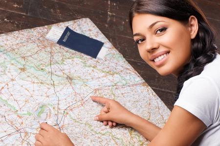 Mulher de sorriso bonita escolhendo seu destino traver com o mapa e lupa Banco de Imagens