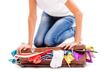 femme valise: Close-up de la jeune fille assise sur la valise et d'essayer de l'emballer, isol� sur blanc