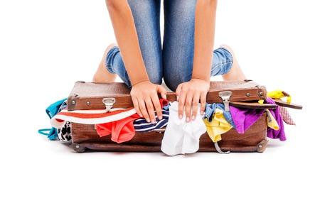mujer con maleta: Primer plano de las piernas de la muchacha que se sientan en la maleta, aislado en blanco