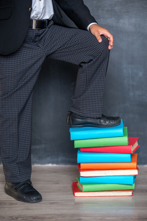 School boy standing with one leg on books in classroom