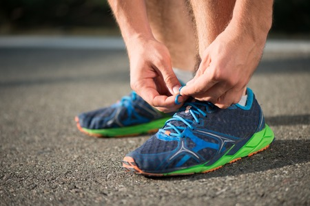 Running shoes on runner. Close-up of sport shoes outdoors on man runner during run Stock Photo