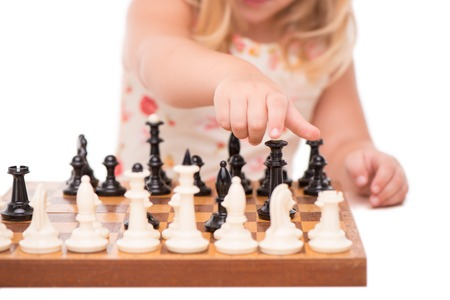 battling: Close-up of little girl hand reaching for black chess figure in a chess game