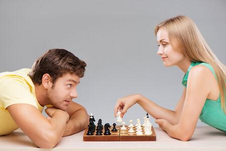 jugando ajedrez: Mujer joven que hace jaque mate a su marido mientras que juega ajedrez Foto de archivo