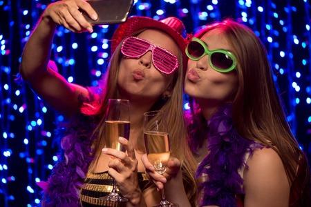 Duas belas mulheres jovens com ta�as de champanhe tomada selfie na festa em boate Banco de Imagens