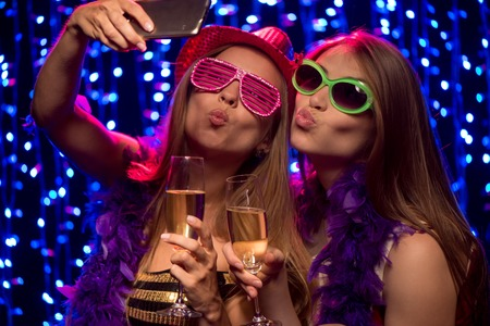Two beautiful young women with glasses of champagne making selfie at party in night club Standard-Bild