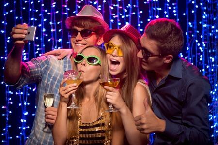 Gruppe von schönen jungen Frauen und Männer machen Selfie auf Party im Nachtclub