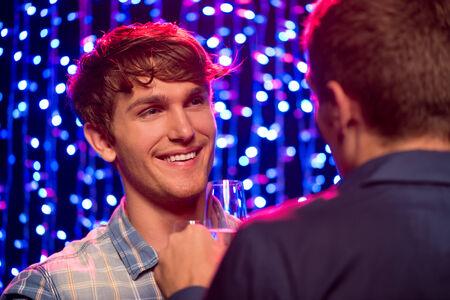 amigas conversando: Dos hombres j�venes hermosas que una conversaci�n amistosa en la fiesta en el club nocturno