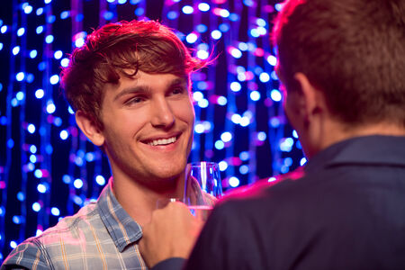 Two beautiful young men having a friendly conversation at party in night club Stock Photo