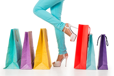 Woman standing with a row of colorful shopping bags, isolated on white background photo