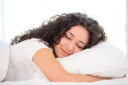 Beautiful happy young woman sleeping in white bed with window as a background