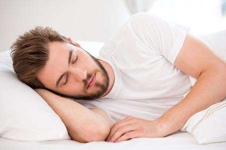 Gut aussehender junger Mann mit einem Bart schlafend im weißen Bett Standard-Bild