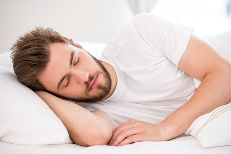 only one man: Handsome young man with a beard sleeping in white bed