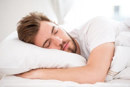 Gut aussehender junger Mann mit einem Bart schlafend im weißen Bett Lizenzfreie Bilder
