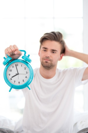 Young man holding alarm clock  in the morning. Concept of sleeping the day away photo