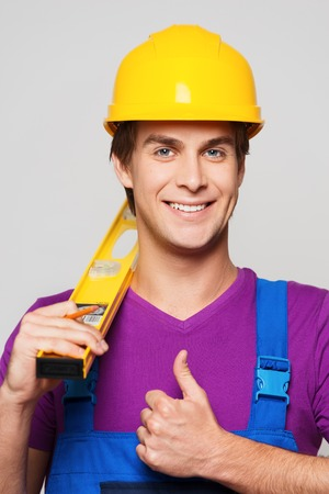 Young smiling repairman in hard hat holding measurement and showing thumb up
